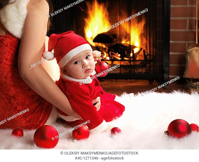 Mother and a little baby boy sitting in front of a fireplace in Christmas costumes