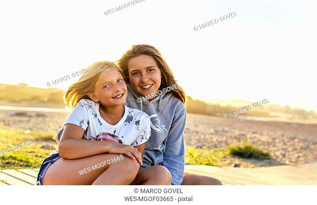 Portrait of two smiling girls sitting on boardwalk