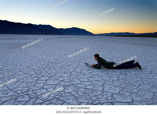 Man lying down using laptop on the salt pans at dawn