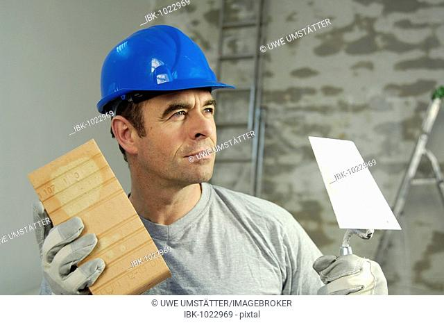 Workman wearing a hard hat, holding a brick trowel and a brick