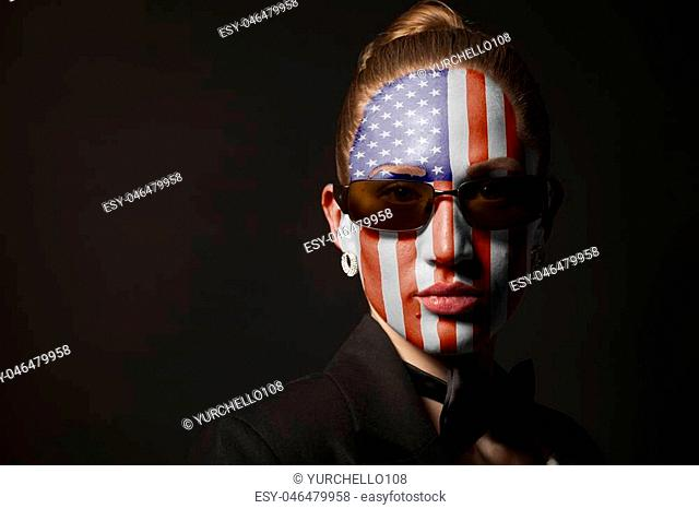 Portrait of woman with painted USA flag and sunglasses on black background