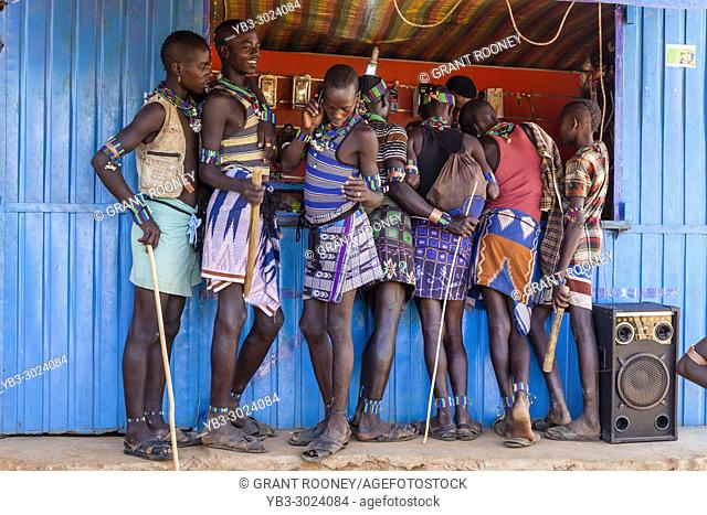 Young Hamar Men Outside A Mobile Phone (Cell Phone) Shop During Their Weekly Visit To The Tribal Market In Dimeka, Omo Valley, Ethiopia