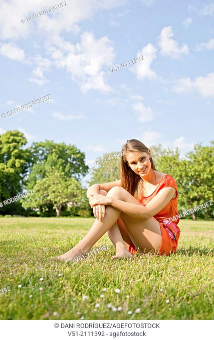 Brunette pretty woman in park smiling at camera