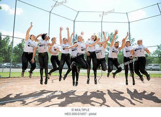 Portrait cheering middle school girl softball team jumping on baseball diamond