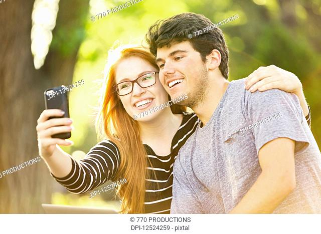 A young man and young woman taking a self-portrait on a smart phone; Edmonton, Alberta, Canada