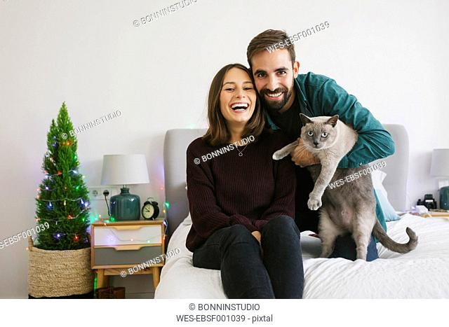 Portrait of couple and their cat at home