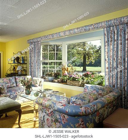 LIVING ROOM - Traditional Living Room - floral chintz upholstered matching sofas and drapery, gathered fabric on curtain rod, yellow walls, textured ceiling