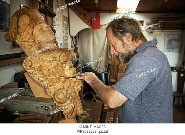A craftsman, a wood carver working on a wooden female ship's figurehead held in a vice on the workbench of his workshop