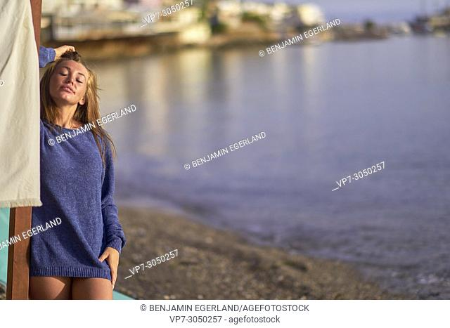 sensual young woman in pullover enjoying beach sun. Russian ethnicity. In holiday destination Hersonissos, Crete, Greece