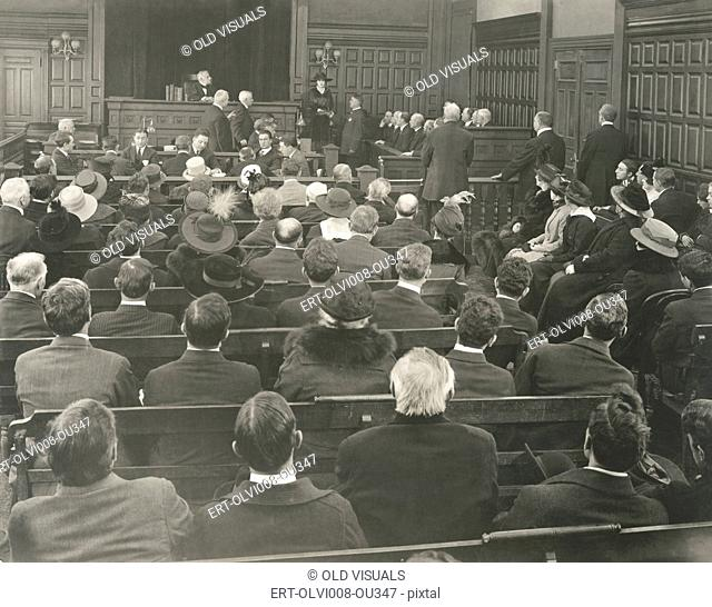 People sitting on benches in courtroom (OLVI008-OU347-F)