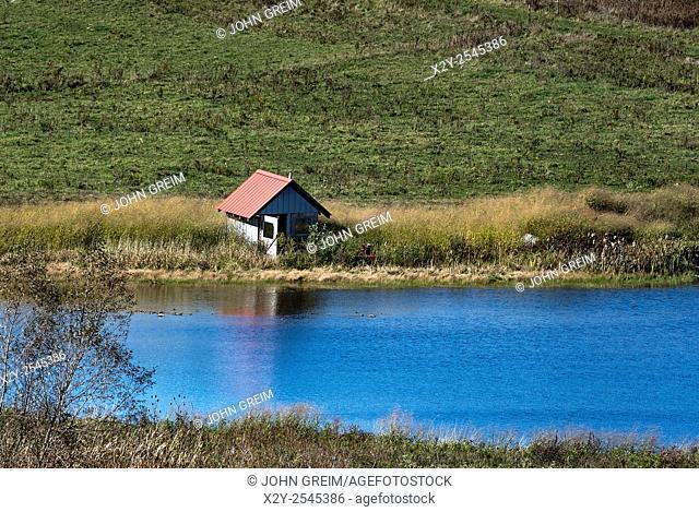 Pump house on rural pond, Richfield Springs, New York, USA