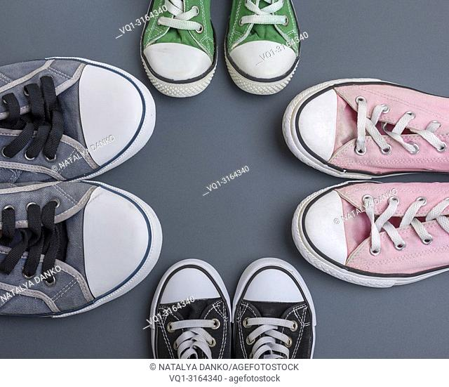four pairs of old textile sneakers on a black background, women's, men's and children's shoes, copy space