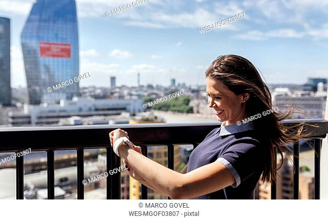 UK, London, happy woman using smartwatch on a roof terrace