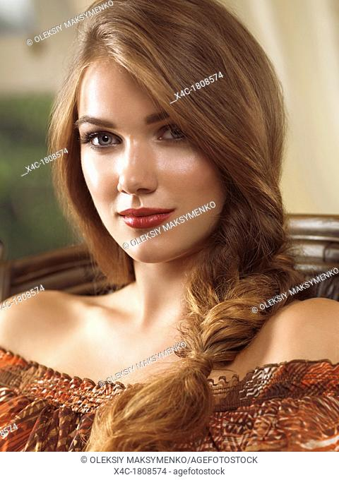 Beauty portrait of a young woman with long hair in a braid sitting in a chair