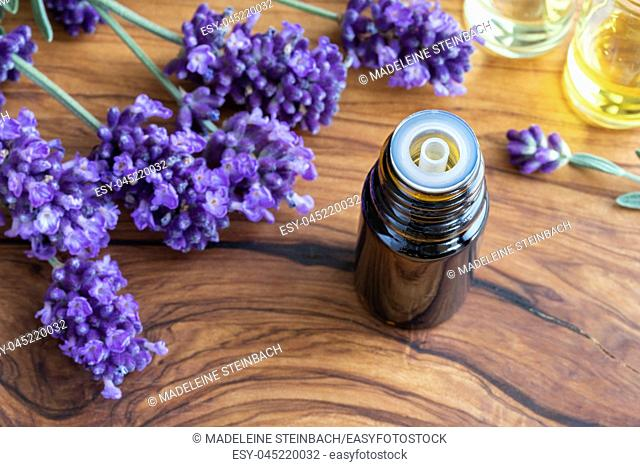 A bottle of essential oil with fresh blooming lavender on a table