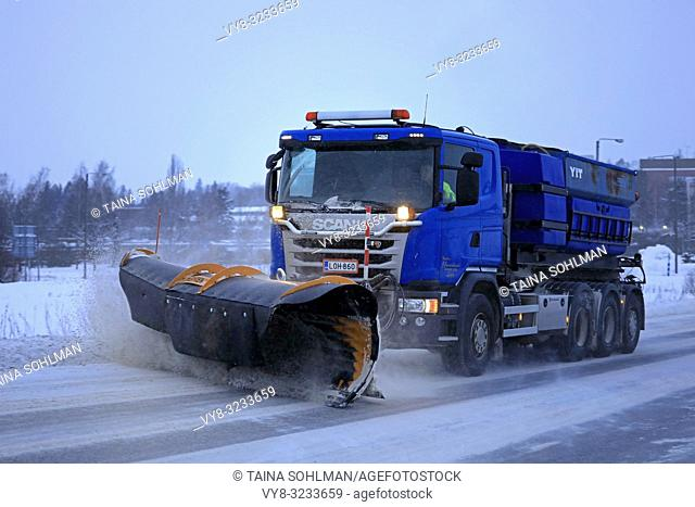 Salo, Finland - January 26, 2019: Blue Scania truck of equipped with snowplow clears a snowy road in suburban area on a winter afternoon