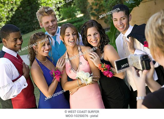 Well-dressed teenagers posing for video camera outside school dance