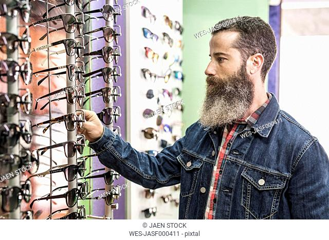 Bearded man in optical store chosing glasses