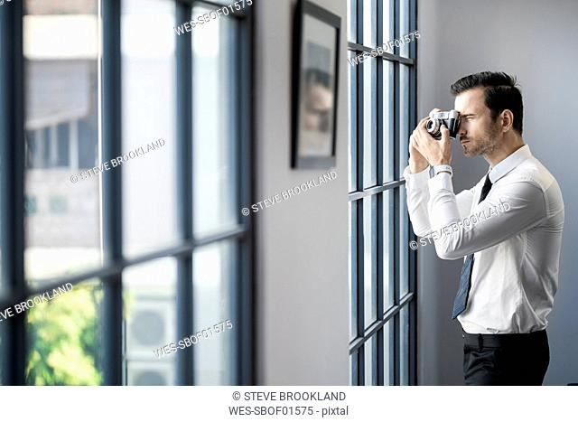 Businessman taking picture with vintage retro camera in front of large office window
