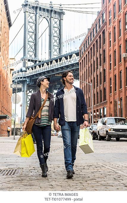 Couple walking on street, Brooklyn Bridge in background