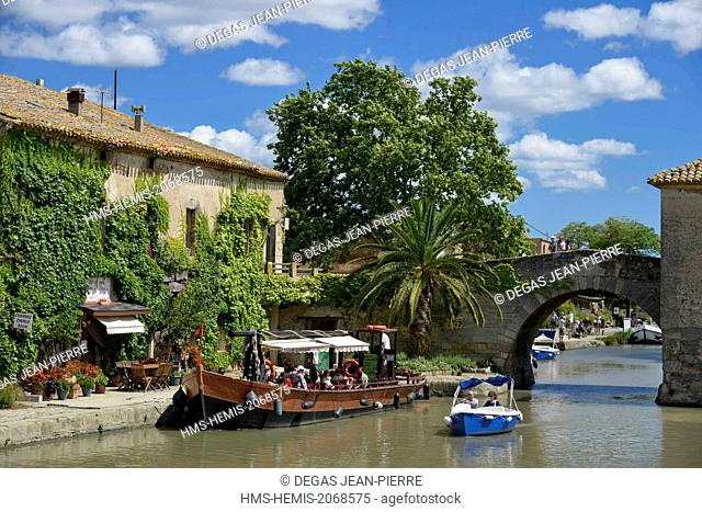 France, Aude, Saint Nazaire d'Aude, Canal du Midi listed as World Heritage by UNESCO, Port of Somail, boats of tourism in front of a building in murx covered...