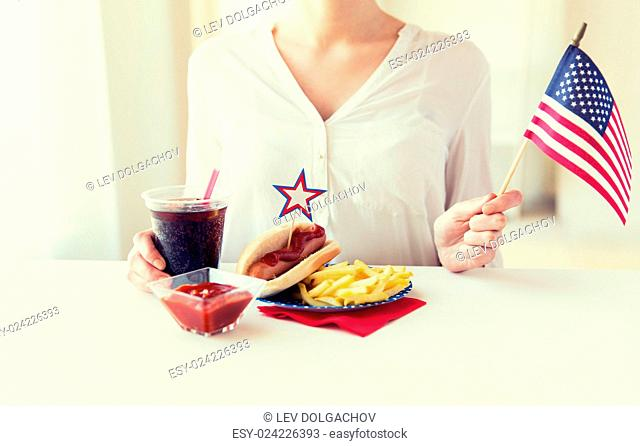 independence day, celebration, patriotism and holidays concept - close up of woman hands with hot dog and french fries holding american flag and cola drink on...