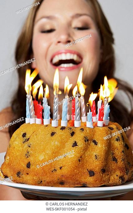 Germany, Berlin, Young woman with birthday cake, smiling