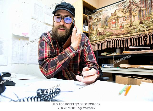 Rotterdam, Netherlands. Coordinator and Boss of Via Kunst urban art place working from his office desk to coordinate operations