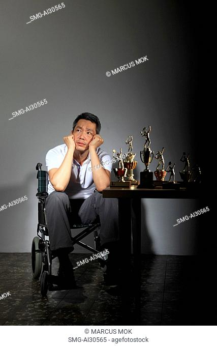 Mature man sitting in a wheelchair looking sad with trophies on a table