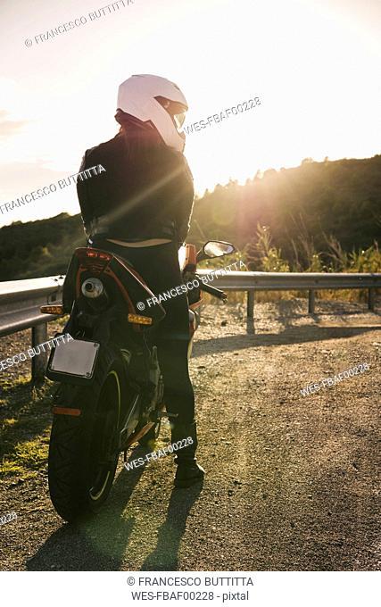 Italy, Elba Island, female motorcyclist at viewpoint