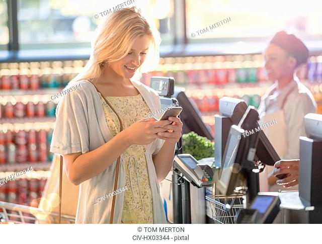 Smiling young woman texting with cell phone at grocery store market checkout