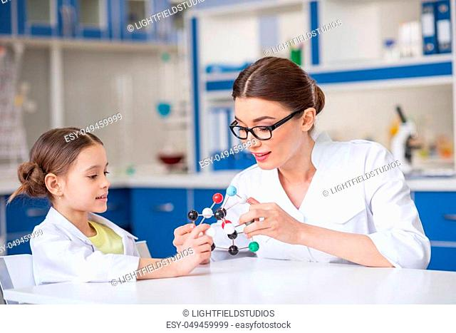 Smiling woman and little girl in lab coats working with molecular model