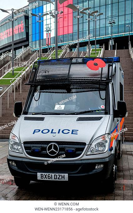 The Metropolitan Police deploy a riot van with a Remembrance Poppy as they patrol the area surrounding Wembley Stadium. The stadium is lit up with French...