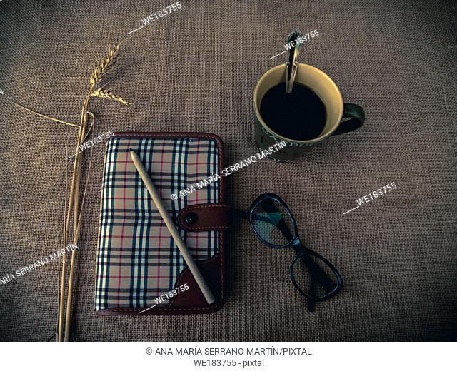 Vintage style. Organized desk with closed diary, eye glasses, a cup of coffee, dry grass, pencil and burlap background