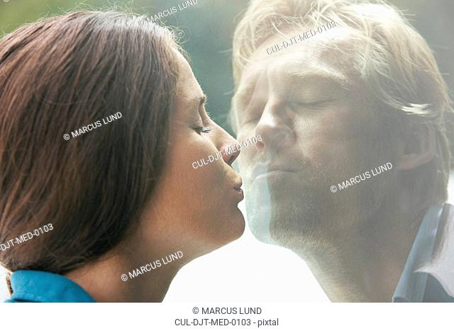 Young couple kissing through glass of window