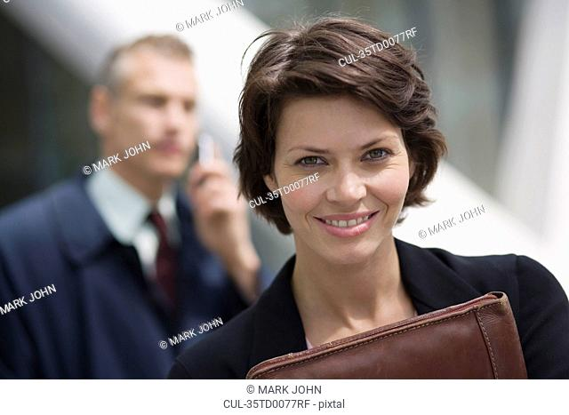 Businesswoman carrying leather folder