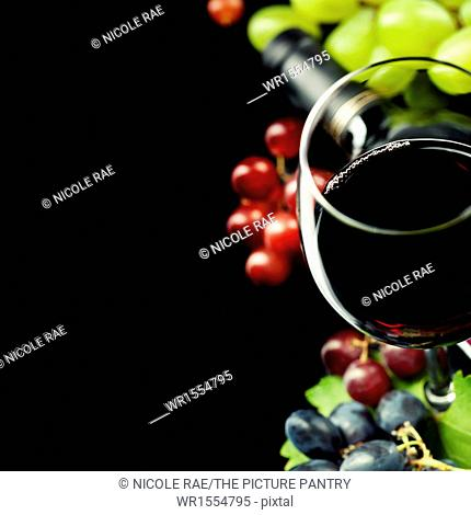 Glasses of wine and grape on black background