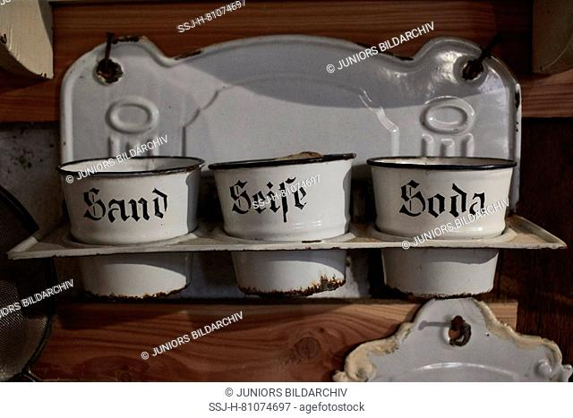 Old enamel holders and shelf with sand, soda and soap. Germany