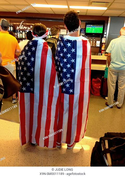 Two Patriotic USA Soccer Fans, a Man and a Woman, Draped in American USA Flags, Watching the USA-Belgium World Cup Soccer Match, in an Airport Bar