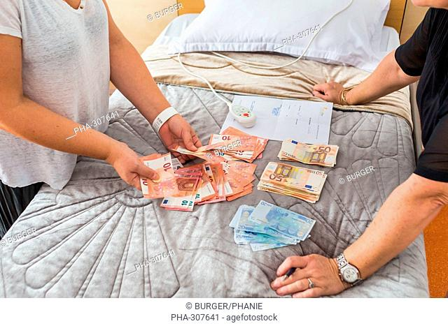Woman paying in cash a cosmetic surgery abroad