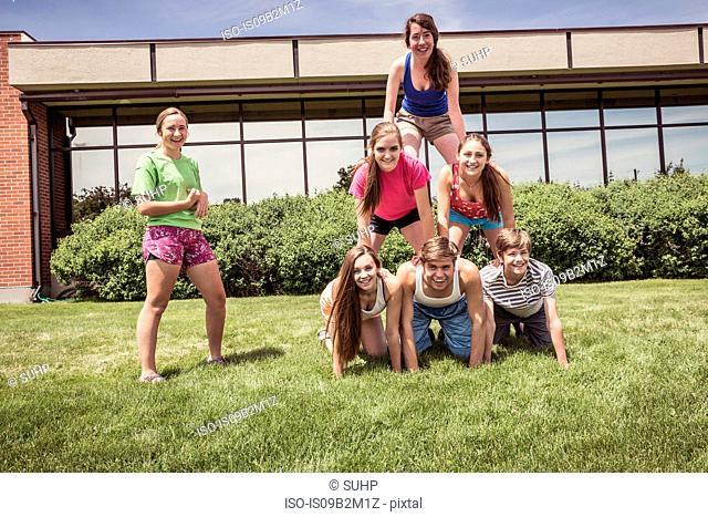 Portrait of teenage high school pupils making human pyramid outside school