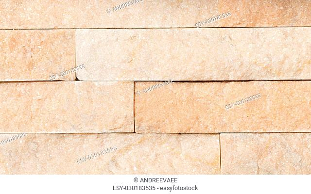 beautiful natural light from a wall of decorative slate stone with a rough textured surface shiny light peach color