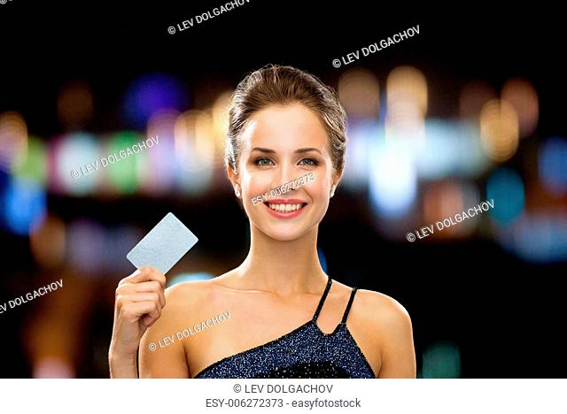 shopping, wealth, money, luxury and people concept - smiling woman in evening dress holding credit card over night lights background