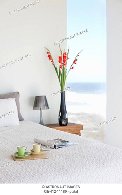 Breakfast tray on bed in modern bedroom with ocean view