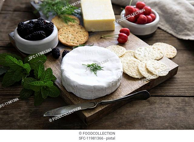 A cheese platter with sesame seed and wheat crackers, herbs, cherries and blackberries