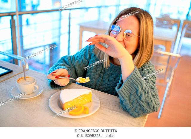 Female higher education student laughing while eating cake in university cafe