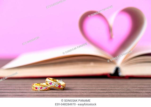 Pages of book curved into a heart shape and wedding ring . Love concept of heart shape from book pages