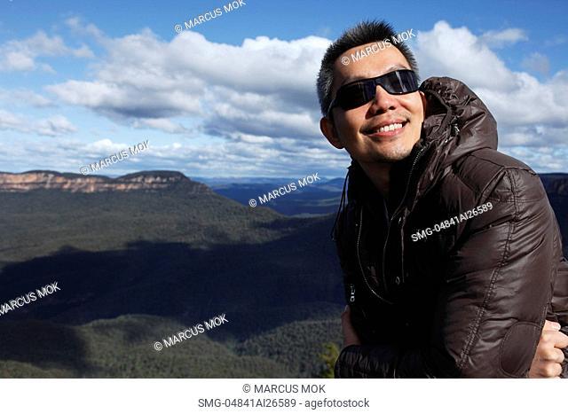 Chinese man wearing jacket smiling in front of mountain range