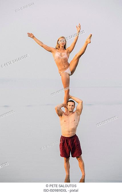 Young couple on beach, woman balancing on one leg, on man's shoulder
