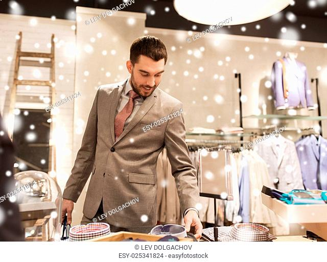 sale, shopping, fashion, style and people concept - happy elegant young man or businessman in suit choosing shirt in mall or clothing store over snow